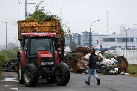 FILE PHOTO:  French farmers, members of the FNSEA, the country's largest farmers' union, block with their tractors the access of the French oil giant Total refinery in Donges, France, June 11, 2018.   REUTERS/Stephane Mahe
