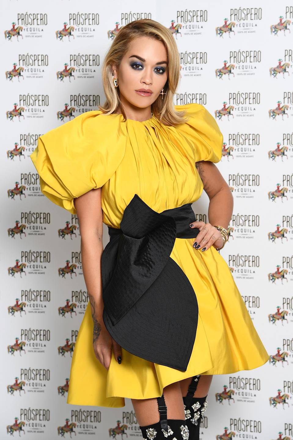 Rita Ora wears a yellow mini dress with a black bow sash at the Prospero Tequila UK Launch on November 23, 2020 in London, England