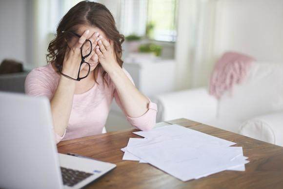 Woman at a laptop with papers in front of her, holding her head