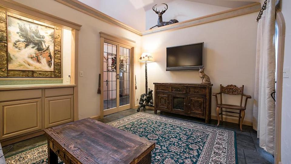 One of the common rooms in the residence, decorated with art, antiques and a flat-screen TV. - Credit: Courtesy of Airbnb