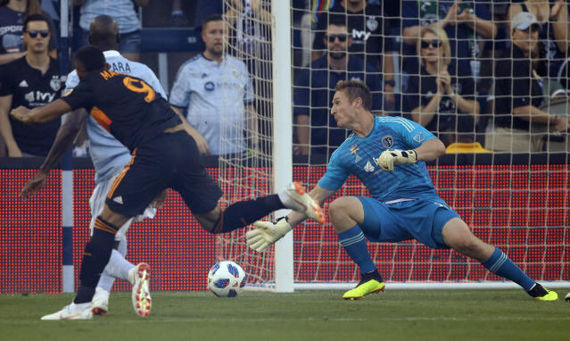 Houston Dynamo forward Mauro Manotas (9) scores past Sporting Kansas City goalkeeper Tim Melia, right, during the first half of an MLS soccer match in Kansas City, Kan., Saturday, June 23, 2018. (AP Photo/Orlin Wagner)