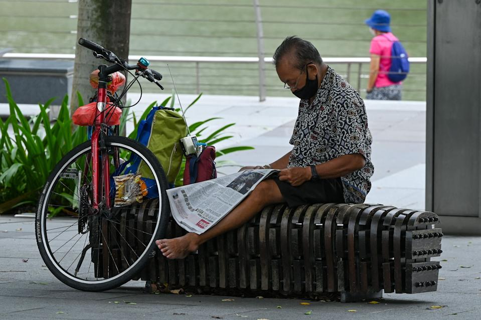 A man sits on a bench reading a newspaper in Singapore on July 14, 2021. (Photo by Roslan Rahman / AFP) (Photo by ROSLAN RAHMAN/AFP via Getty Images)