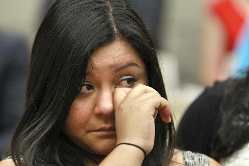 Myrna Orozco, 22, of Kansas City, Mo., an illegal immigrant originally from Mexico, wipes away tears while watching President Obama announce that the U.S. government will stop deporting and begin granting work permits to younger illegal immigrants who came to the U.S. as children and have since led law-abiding lives, Friday, June 15, 2102, in Washington. (AP Photo/Jacquelyn Martin)