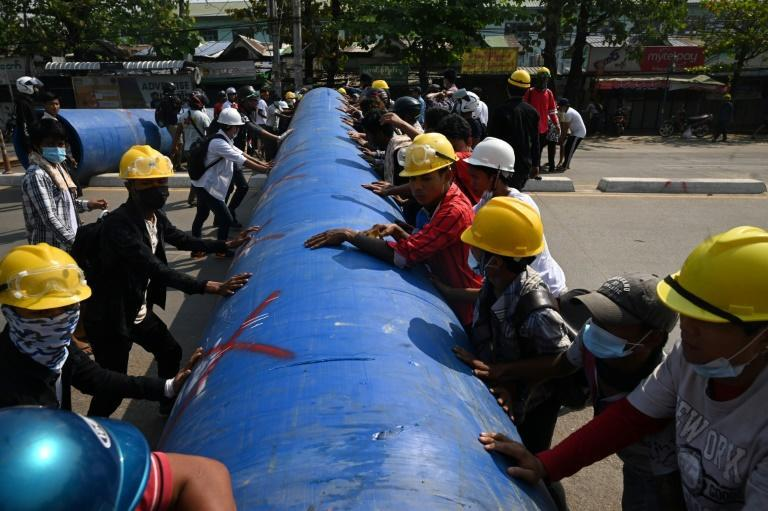 Anti-coup protesters in Myanmar rolled a large pipe into a Yangon street to build a barricade