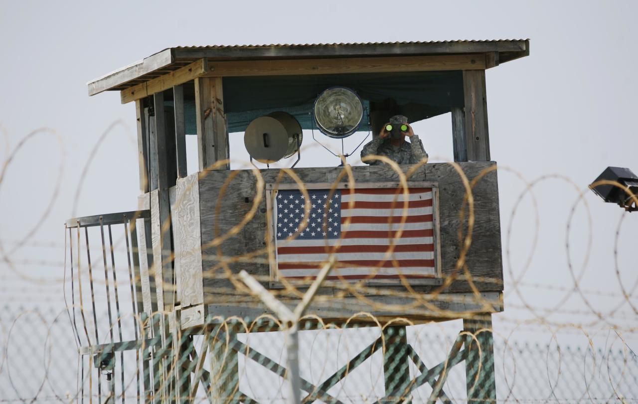 FILE - In this May 13, 2008 file photo reviewed by the U.S. Military, a U.S. Army soldier looks through binoculars while standing on a guard tower at Camp 4 in the Guantanamo Bay US Naval Base in Cuba. Five men accused of orchestrating the Sept. 11 attacks, including the self-proclaimed mastermind, are headed back to a military tribunal at Guantanamo Bay more than three years after President Barack Obama put the case on hold in a failed effort to move the proceedings to a civilian court and close the prison at the U.S. base in Cuba. (AP Photo/Rodrigo Abd, file)