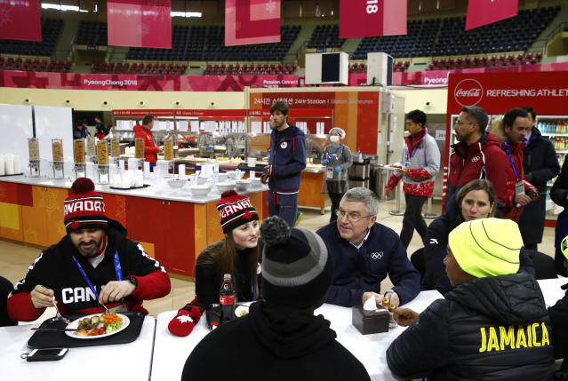 <p>International Olympic Committee President Thomas Bach, second from right, visits with members of the Canadian and Jamaican Olympic teams as they eat lunch during a tour of the PyeongChang Olympic Village. (AP) </p>