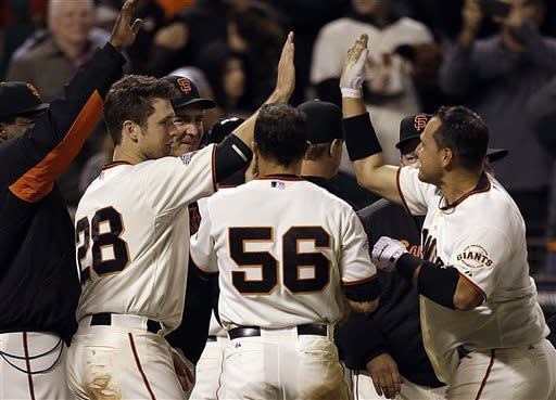 San Francisco Giants' Guillermo Quiroz, right, celebrates with teammates including Buster Posey (28) after Quiroz hit the game winning home run in the tenth inning of a baseball game against the Los Angeles Dodgers Saturday, May 4, 2013, in San Francisco. (AP Photo/Ben Margot)