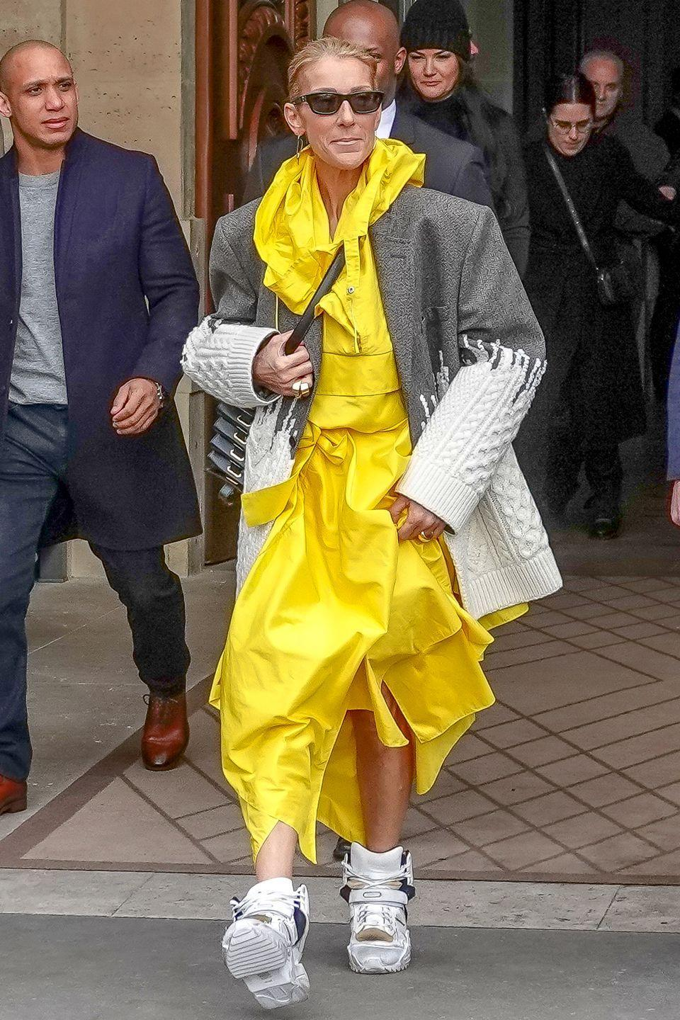 <p>Perhaps a nod to Billie Eilish's signature oversized wardrobe, Dion stepped out in Paris wearing a boxy grey blazer, bright yellow dress, and chunky sneakers.</p>