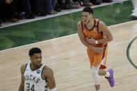 Phoenix Suns guard Devin Booker celebrates in front of Milwaukee Bucks forward Giannis Antetokounmpo (34) during the second half of Game 4 of basketball's NBA Finals Wednesday, July 14, 2021, in Milwaukee. (AP Photo/Aaron Gash)