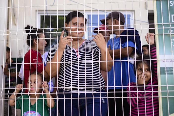 A Central American family waits to be granted asylum or a humanitary visa at the immigration office on the Mexico-Guatemala international bridge in Ciudad Hidalgo, Chiapas State, Mexico (AFP Photo/Pedro PARDO)