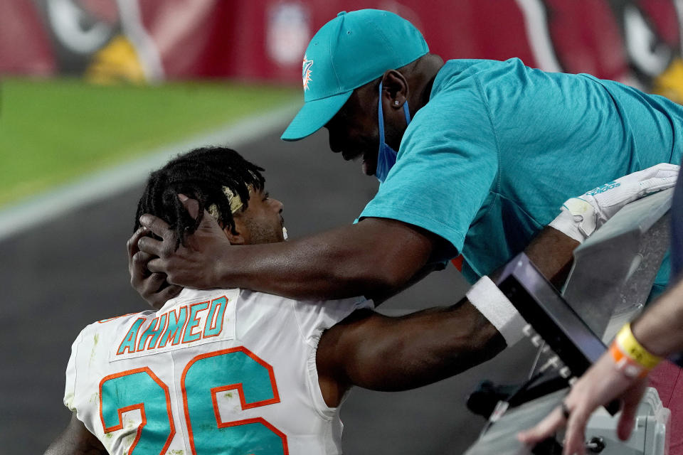 Salvon Ahmed hugs his dad, Randy, who is in the stands. Neither has a mask covering their nose and mouth. Randy's mask is on his chin.