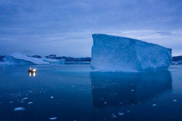 PHOTO: A boat navigates at night next to large icebergs in eastern Greenland, Aug. 15, 2019. (Felipe Dana/AP, FILE)