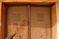 A finger points at bullet holes at the Government Science school in Kankara