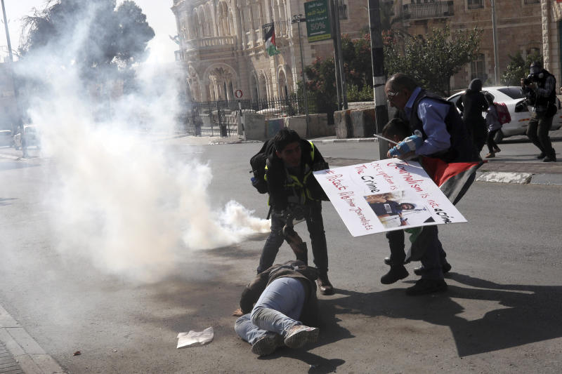 Palestinian journalists help a colleague who fell running away from tear gas and sound bombs thrown by Israeli border police during a journalist's protest in support of a 35 year-old photographer Muath Amarneh in Bethlehem, West Bank, Sunday, Nov. 17, 2019. Amarneh's relatives say he has lost vision in one eye after apparently being struck by Israeli fire while covering a demonstration in the West Bank. Israel's paramilitary border police unit says it did not target him. (AP Photo/Mahmoud Illean)