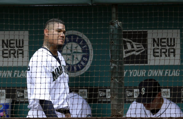 Seattle Mariners starting pitcher Felix Hernandez, left, walks through the dugout after being pulled in the fourth inning of a baseball game, against the Texas Rangers, Wednesday, Aug. 28, 2013, in Seattle. (AP Photo/Ted S. Warren)