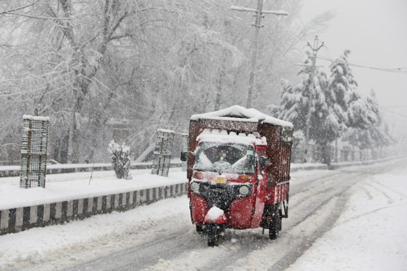 An auto-rickshaw drives on a snow-covered road on the outskirts of Srinagar, Indian controlled Kashmir, Thursday, Feb. 7, 2019. The fresh snowfall has resulted in disruption of air and road traffic for the second consecutive day between Srinagar and Jammu, the summer and winter capitals of India's troubled state. (AP Photo/ Dar Yasin)