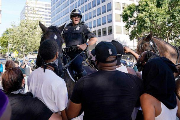 PHOTO: Police on horseback face demonstrators outside the site of the Democratic National Convention, Aug. 20, 2020, in Milwaukee. (Morry Gash/AP)