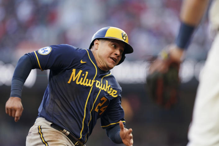 Milwaukee Brewers' Avisail Garcia (24) heads home on an RBI single hit by Milwaukee Brewers Omar Narvaez during the fourth inning of Game 4 of a baseball National League Division Series against the Atlanta Braves, Tuesday, Oct. 12, 2021, in Atlanta. (AP Photo/Brynn Anderson)