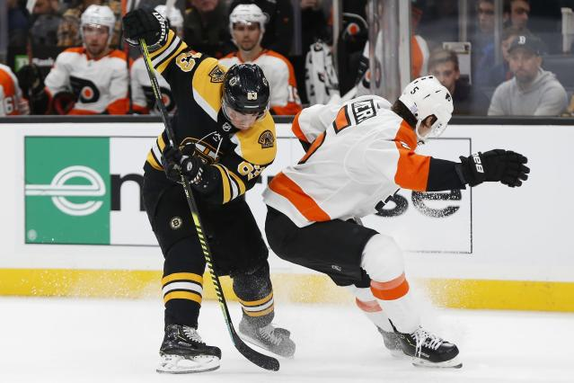 Boston Bruins' Brad Marchand (63) and Philadelphia Flyers' Philippe Myers (5) battle for the puck during the first period of an NHL hockey game in Boston, Sunday, Nov. 10, 2019. (AP Photo/Michael Dwyer)