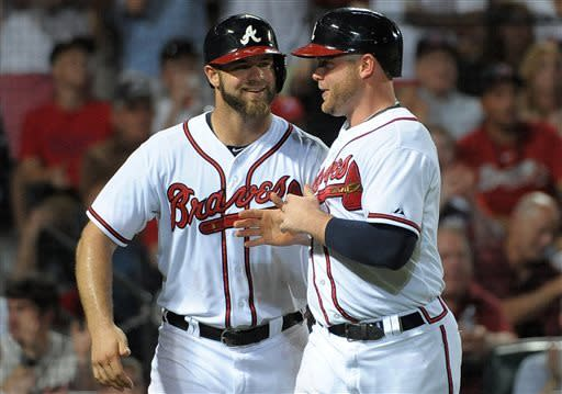 CORRECTS INNING TO SEVENTH - Atlanta Braves' Evan Gattis and Brian McCann, right, smile after scoring against the Toronto Blue Jays in the seventh inning of a baseball game at Turner Field in Atlanta, Thursday, May 30, 2013. (AP Photo/David Tulis)