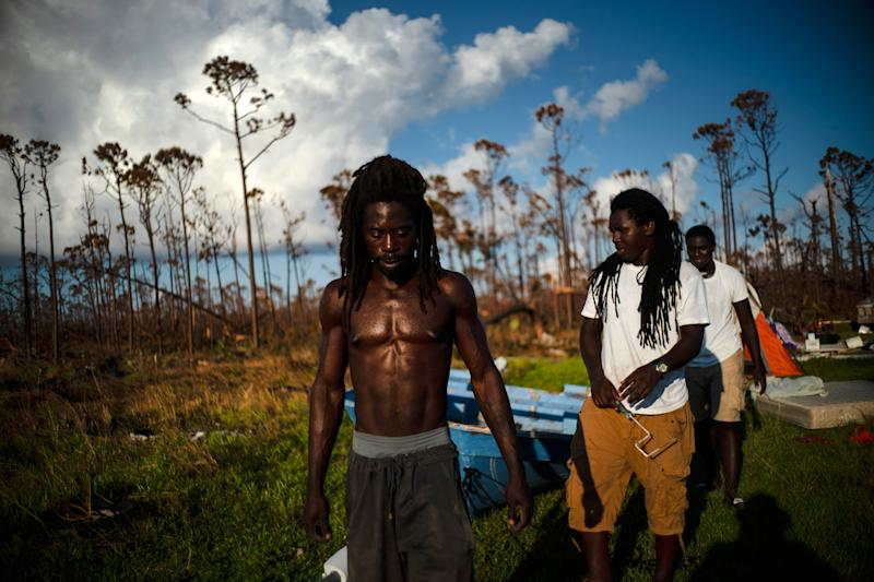 Dexter Edwards, front, his brother Nathanael Edwards right, and his cousin Valentino Ingraham walk amid one of their family's homes destroyed by Hurricane Dorian in Rocky Creek East End, Grand Bahama, Bahamas, Sept. 8, 2019.