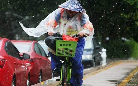 A Chinese sanitation worker rides a bicycle against the strong wind caused by Typhoon Hato on a road along the seacoast in Zhuhai in China's southern Guangdong province - Credit: AFP