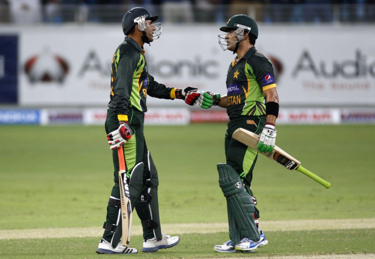 Pakistan's Abdul Razzaq (L) chats with Umar Akmal (R) during their first Twenty20 international cricket match against South Africa in Dubai November 13, 2013. REUTERS/Nikhil Monteiro (UNITED ARAB EMIRATES - Tags: SPORT CRICKET)