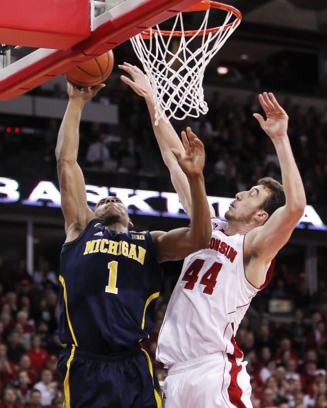 Michigan's Glenn Robinson III (1) shoots against Wisconsin's Frank Kaminsky during the first half of an NCAA college basketball game Saturday, Jan. 18, 2014, in Madison, Wis. (AP Photo/Andy Manis)