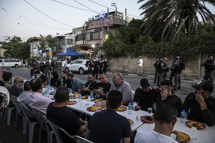 Palestinians sit at a large table to break the fast during Ramadan as Israeli border police guard Jewish settlers, outside one of the homes they have taken over from a Palestinian family and by other homes of Palestinians facing eviction, in the East Jerusalem neighborhood of Sheikh Jarrah on May 7, 2021.