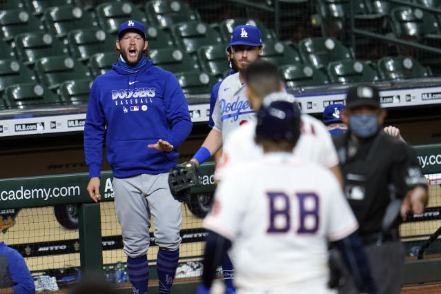 Los Angeles Dodgers' Clayton Kershaw, left, yells toward Houston Astros' Carlos Correa after the sixth inning of a baseball game Tuesday, July 28, 2020, in Houston. Both benches emptied onto the field during the exchange. (AP Photo/David J. Phillip)