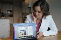 Dr. Michelle Rockwell, who was targeted by vaccine opponents after she posted about her miscarriage online, looks at her Instagram page with her hijacked post marked as fake news during an interview at her home Wednesday, April 28, 2021, in Jenks, Okla. Individuals across the country, like Rockwell, have found themselves swept into the misinformation maelstrom, their online posts or their very identities hijacked by anti-vaccine activists and others peddling lies about the COVID-19 outbreak. (AP Photo/Sue Ogrocki)