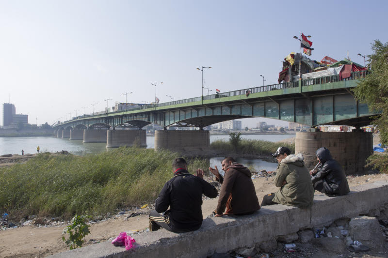 Anti-government protesters camp behind cement blocks, on the right side of a bridge, that separate them from riot police, on the left side, during the ongoing protests in Tahrir Square, Baghdad, Iraq, Thursday, Dec. 26, 2019. (AP Photo/Nasser Nasser)