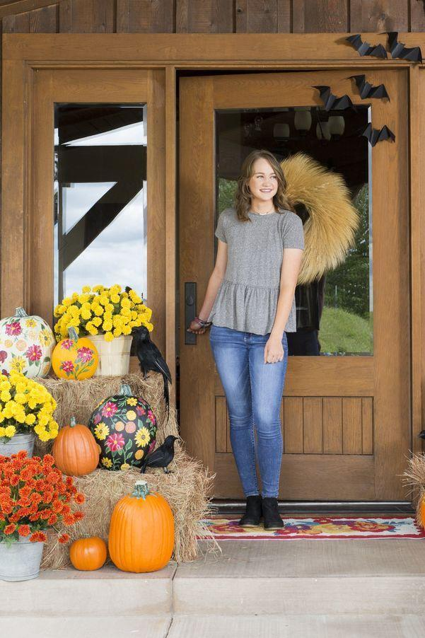 """<p>Get inspired by Ree's own front door! This photo is from a few Halloweens ago (yes, that's really Paige!), but that oversized wreath and those fluttering bats are still just as elegant today.</p><p><a class=""""link rapid-noclick-resp"""" href=""""https://go.redirectingat.com?id=74968X1596630&url=https%3A%2F%2Fwww.walmart.com%2Fsearch%2F%3Fquery%3Dwheat%2Bwreaths&sref=https%3A%2F%2Fwww.thepioneerwoman.com%2Fholidays-celebrations%2Fg32894423%2Foutdoor-halloween-decorations%2F"""" rel=""""nofollow noopener"""" target=""""_blank"""" data-ylk=""""slk:SHOP WHEAT WREATHS"""">SHOP WHEAT WREATHS</a></p>"""