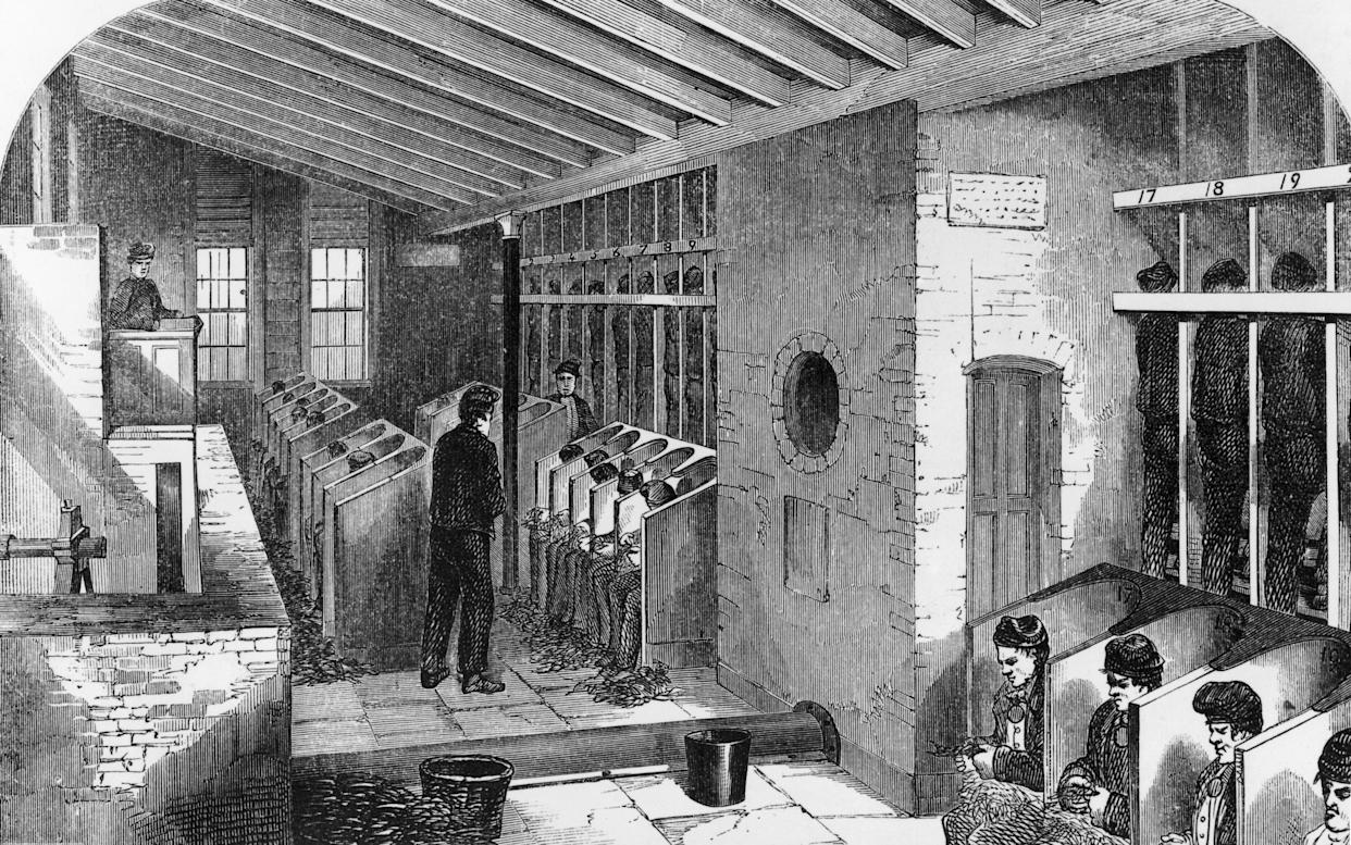Prisoners on a treadmill (far right) and picking oakum in the oakum shed at Holloway Prison, London, 1862. Oakum picking involves teasing out old tarred rope to be used for caulking ships. (Photo by Hulton Archive/Getty Images)