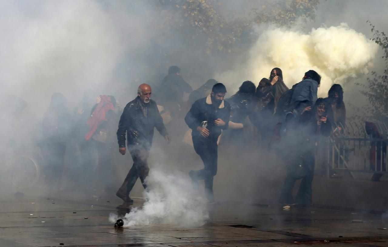Protesters move away from tear gas during a protest in front of a courthouse in Ankara October 28, 2013. Turkish police fired water cannon and teargas on Monday to break up the protest by around 2,000 people outside the court over the handling of the trial of a policeman accused of killing a demonstrator earlier this year. Officer Ahmet Sahbaz is accused of killing Ethem Sarisuluk, shot dead in June during a wave of nationwide anti-government demonstrations set off by a tough police response to a protest over the redevelopment of a park in Istanbul. REUTERS/Umit Bektas (TURKEY - Tags: POLITICS CIVIL UNREST CRIME LAW)