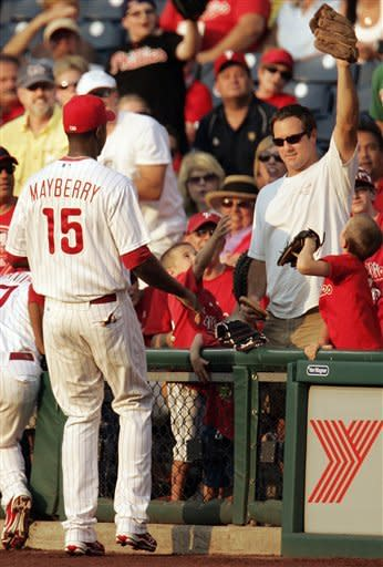 Philadelphia Phillies' John Mayberry, left, looks at a fan holding up the catch he made of a foul ball in the second inning of a baseball game with the Colorado Rockies, Thursday, June 21, 2012, in Philadelphia. (AP Photo/Tom Mihalek)