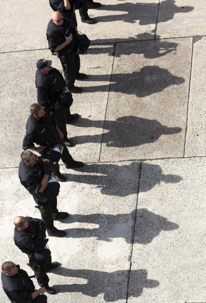 The sun casts the shadows of riot policemen on the street, during demonstrations of a far-right group and counter protesters in front of a mosque in Berlin, Germany, Saturday, Aug. 18, 2012. (AP Photo/Gero Breloer)
