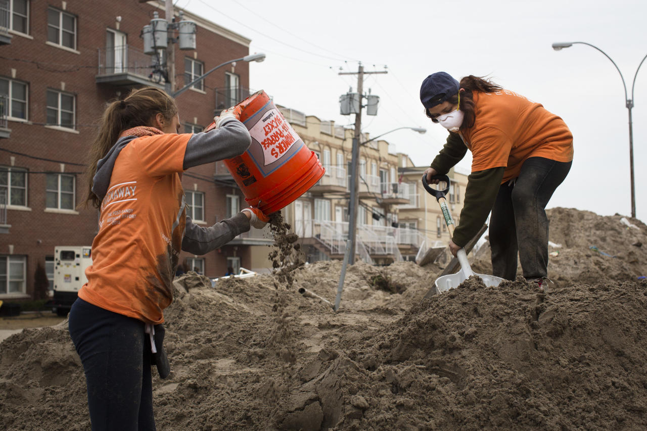 Volunteers work to remove sand from streets in the Rockaways, Saturday, Nov. 10, 2012, in the Queens borough of New York. Despite power returning to many neighborhoods in the metropolitan area after Superstorm Sandy crashed into the Eastern Seaboard, many residents of the Rockaways continue to live without power and heat due to damage caused by Sandy. (AP Photo/John Minchillo)