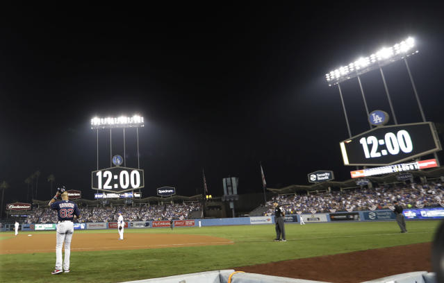 A clock in Dodger Stadium turns to midnight at the beginning of the 17th inning in Game 3 of the World Series baseball game between the Boston Red Sox and Los Angeles Dodgers on Saturday, Oct. 27, 2018, in Los Angeles. (AP Photo/David J. Phillip)