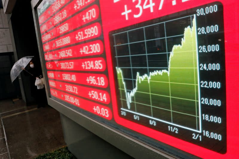 FILE PHOTO: A woman holding umbrella walks near an electric board showing Nikkei index at a brokerage in Tokyo