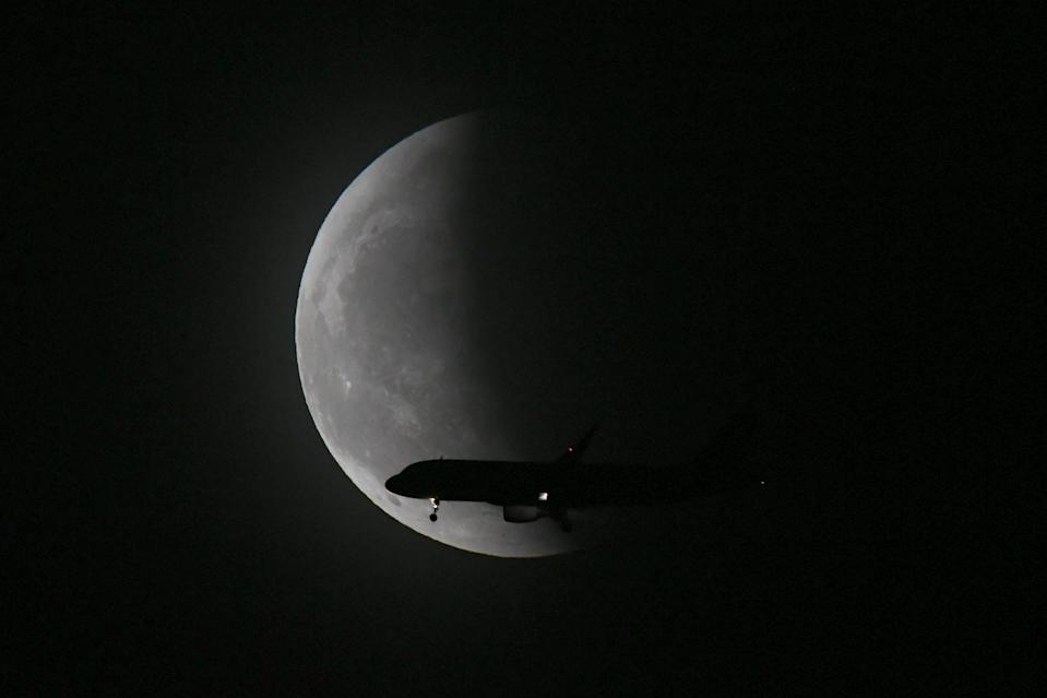 <p>SHENYANG, CHINA - MAY 26: A plane flies past the super moon during the total lunar eclipse on May 26, 2021 in Shenyang, Liaoning Province of China. (Photo by VCG/VCG via Getty Images)</p>