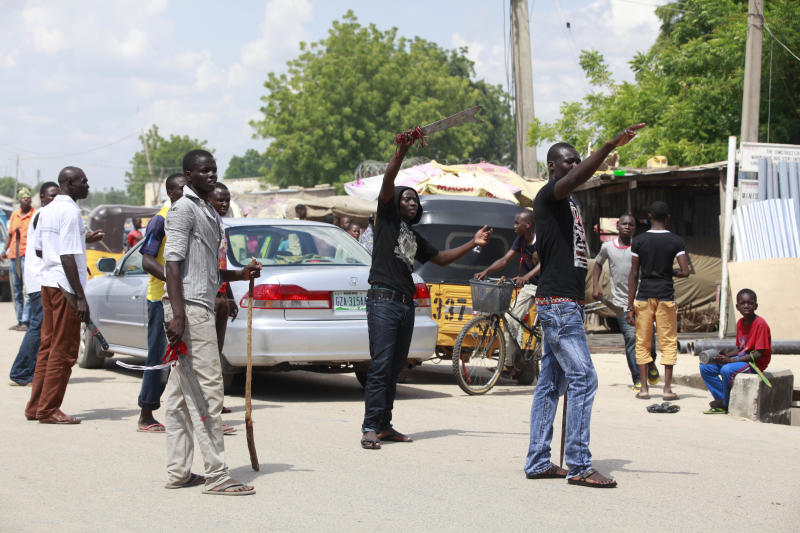 In this photo taken Wednesday, Aug. 7, 2013 Vigilantes Civilian JTF with cutlasses and clubs mount a check point on the street of Maiduguri, Nigeria. The battered old car, cutlasses and nail-studded clubs poking out of its windows, careens down the road and squeals to a stop. Its young occupants pile out, shouting with glee, and set up a roadblock. They are part of a vigilante force that has arisen here as a backlash against Boko Haram, the Islamic extremist network responsible for 1,700 deaths in Nigeria since 2010, according to a count by The Associated Press. (AP Photo/Sunday Alamba)