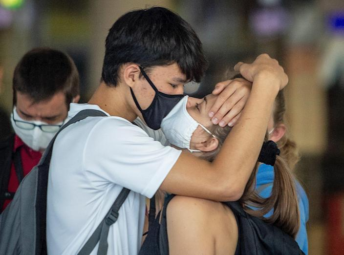 A young couple with face masks kisses goodbye at the airport in Frankfurt, Germany, Aug. 3, 2020.