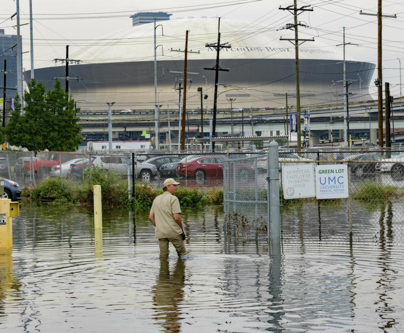 Frank Conforto Jr. walks in the parking lot of the University Medical Center (UMC) with the Mercedes-Benz Superdome in the background on Glavez Street in New Orleans after flooding from a storm, July 10, 2019. (Photo: Matthew Hinton/AP)