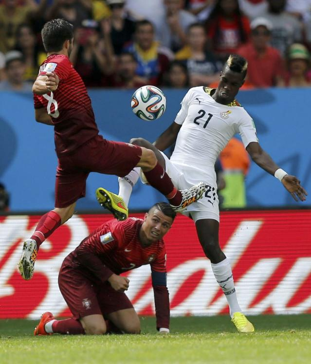 Portugal's Joao Moutinho (L) fights for the ball with Ghana's John Boye (R) as Portugal's Cristiano Ronaldo is seen on the ground during their 2014 World Cup Group G soccer match at the Brasilia national stadium in Brasilia June 26, 2014. REUTERS/Ueslei Marcelino (BRAZIL - Tags: SOCCER SPORT WORLD CUP)