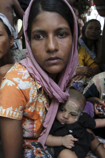 A Muslim refugees woman cuddles a baby at Thechaung camp refugee camp in Sittwe, Rakhine State, western Myanmar, Sunday, Oct. 28, 2012. Boats carrying some of those fleeing arrived outside the state capital, Sittwe. They trudged to the nearby Thechaung camp, a place already home to thousands of Rohingya Muslims who took refuge there after a previous wave of violence in June. (AP Photo/Khin Maung Win)