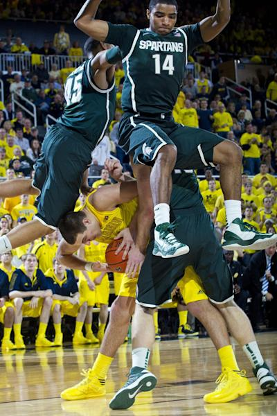 Michigan forward Mitch McGary, bottom, ducks under Michigan State guards Denzel Valentine (45) and Gary Harris (14), in the second half of an NCAA college basketball game on Sunday, March 3, 2013, at Crisler Center in Ann Arbor, Mich. Michigan won 58-57. (AP Photo/Tony Ding)