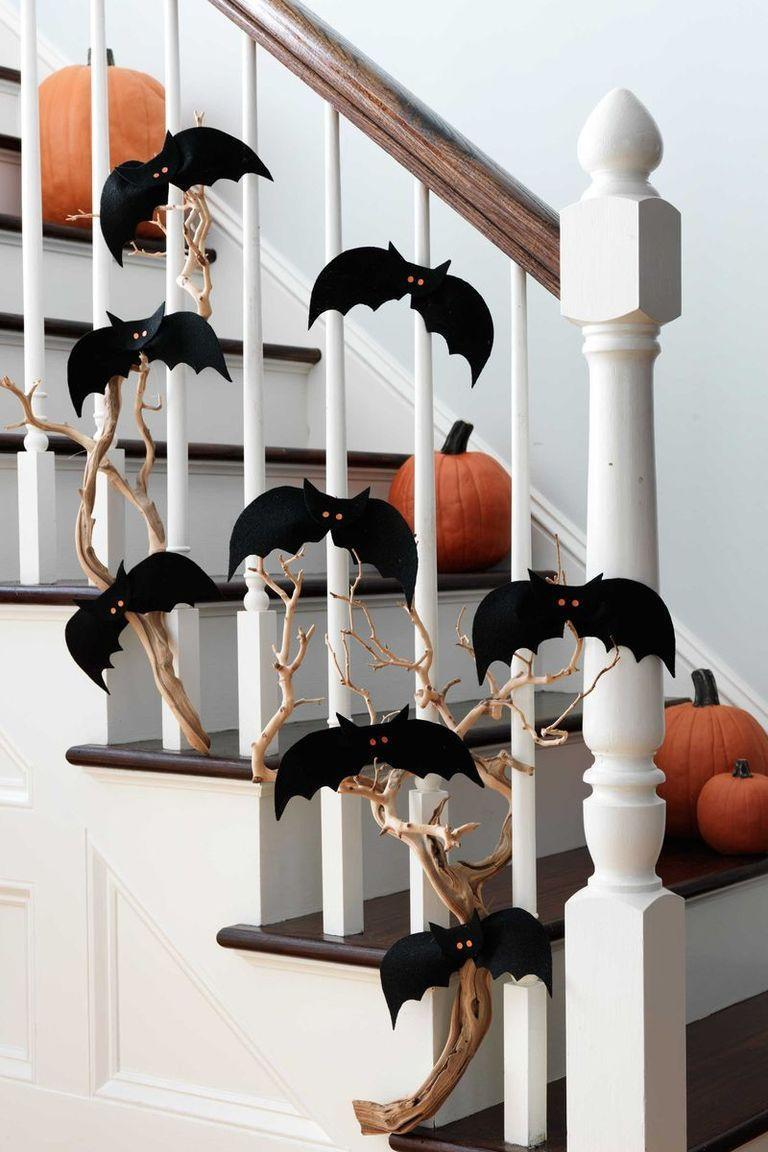 <p>Your staircase is a focal point in your house, so you might as well give it the Halloween treatment. Weave twigs through the banister, and then scatter paper bats throughout to up the spook factor. </p>