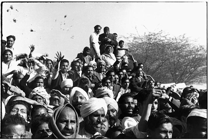 """<p>""""Gandhi's funeral. Crowds gathered between Birla House and the cremation ground, throwing flowers."""" Delhi, India • 1948. (Photo: Henri Cartier-Bresson/Magnum Photos) </p>"""