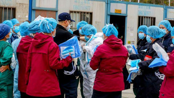 PHOTO: A medical worker puts on a protective suit before entering a sports center which has been converted into a makeshift hospital to treat patients of the novel coronavirus, in Wuhan, Hubei province, China, Feb. 12, 2020. (Stringer/Reuters)